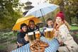 Deutschland, Bayern, Englischer Garten, Vier Personen sitzen in regnerischen Biergarten
