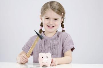 Mädchen mitHammer ist dabei,Sparschwein aufbrechen