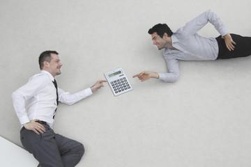 Zwei Geschäftsleute mit Taschenrechner, Seitenansicht