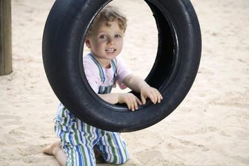 Deutschland, Junge Kleinkind Blick durch Autoreifen am Spielplatz, Portrait