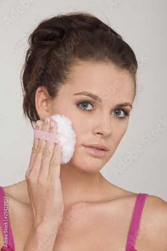 young woman using a powder puff