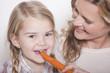 Deutschland, Mutter und Tochter Tochter essen eine Karotte, Portrait, close-up