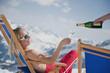 Österreich, Salzburger Land, Junge Frau im Liegestuhl mit Sektglas, Lächeln