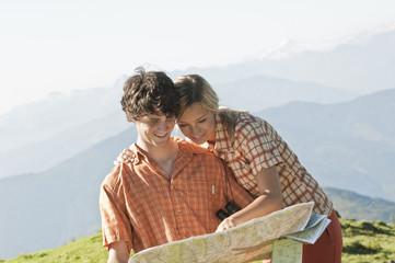 Junges Paar sucht auf einer Karte nach einem Berggipfel