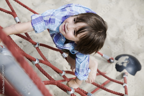 germany, berlin, boy (3-4) at playground climbing on jungle gym, elevated view