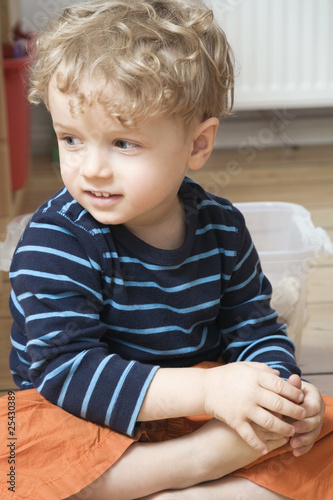 germany, berlin, boy (3-4) sitting on wooden floor, looking away, portrait, close-up