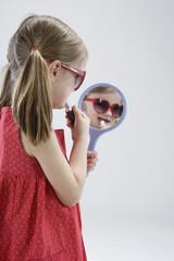 Mädchen Auftragen von Lippenstift mit Handspiegel