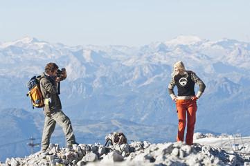 Österreich, Steiermark, Dachstein, Mann fotografiert Frau auf dem Berggipfel