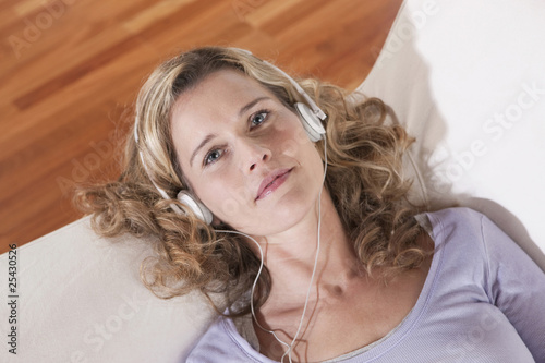 germany, cologne, woman lying on sofa wearing headphones, elevated view