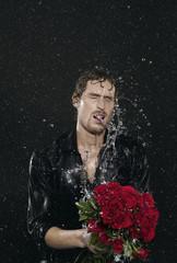 Man steht im Regen, Wetter, hält Blumenstrauß, rote Rosen
