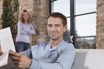 Deutschland, Paar, Mann auf Sofa mit Zeitung, Frau, Porträt, Nahaufnahme