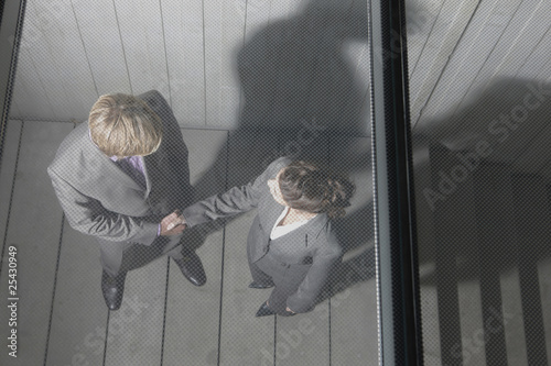 germany, cologne, business people shaking hands on stairway, elevated view