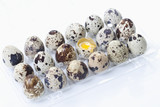 spotted quail eggs in egg box with one broken, elevated view