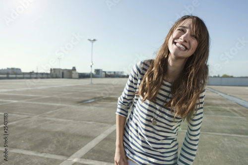 germany, berlin, young woman on parking level, laughing, portrait
