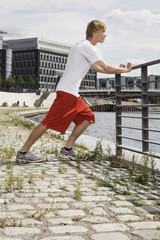 Deutschland, Berlin, Stretching Junger Mann am Geländer