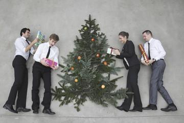 Vier Geschäftsleute mit Weihnachtsgeschenken, stehen um Weihnachtsbaum