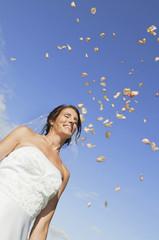 Deutschland, Bayern, Braut lächeln unter fallenden Blütenblättern, Porträt,