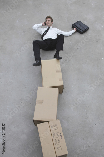 businessman balancing on stack of cardboard boxes, using mobile phone, elevated view