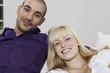 Deutschland, Junges Paar sitzen auf dem Sofa, lächeln, close-up