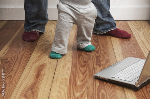 father with son standing by laptop, low section.