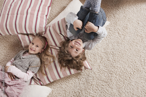germany, cologne, boy and girl (6-7) lying on carpet, elevated view