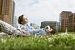 Deutschland, Berlin, Junges Paar auf Wiese, Hochhäusern