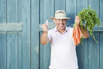 Deutschland, Bayern, Mann vor der Stalltür mit Bund Karotten, Lächeln, Portrait