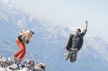 Österreich, Steiermark, Dachstein, Frau macht Foto vom Mann,der springt