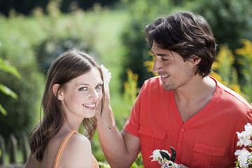 Deutschland, Bayern, Paar im Garten, Mann Platzierung Blume im Haar der Frau, lächeln, Porträt