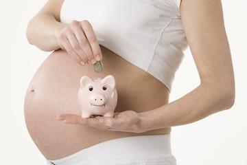 Schwangere Frau halten Sparschwein,