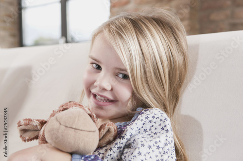 germany, cologne, girl (4-5) with a stuffed toy, sitting on sofa