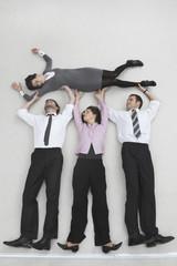 Vier Geschäftsleute, Unternehmer und Unternehmerin heben Kollegen
