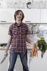 Deutschland, Junger Mann in der Küche mit Bund Karotten und Messer, lachen, Porträt