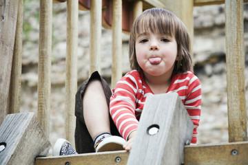 Deutschland, Junge Kleinkind am Klettergerüst Zunge herausstrecken, Portrait