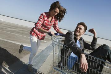 Deutschland, Berlin, Frau jung schieben jung Mann im Einkaufswagen