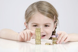 girl (4-5) counting stack of coins