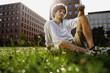 Deutschland, Berlin, Junger Mann entspannen auf dem Rasen, Hochhäuser