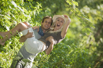 Mann trägt Frau im Wald, lächelnd