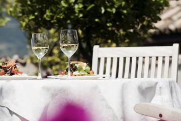 Italien, Südtirol, Gedeckter Tisch, mit gemischtem Salat auf Teller und zwei Gläser mit Weißwein
