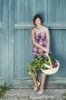 Deutschland, Bayern, Frau vor der Stalltür halten Korb mit frischem Gemüse, lächeln, Porträt