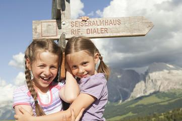 Italien, Seiseralm, Mädchen, stehen durch Wegweiser, Lächeln, Portrait, close-up