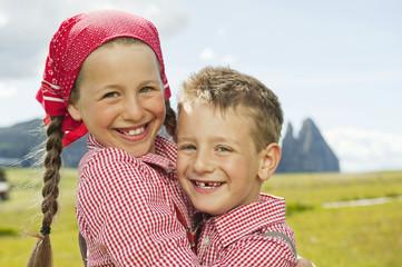 Italien, Seiseralm, Junge und Mädchen im Feld, umarmen, Lächeln, Portrait, close-up