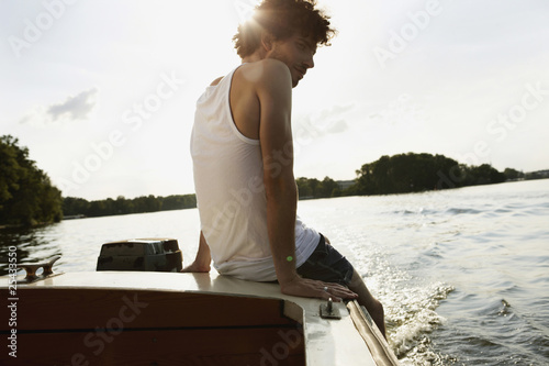 germany, berlin, young man sitting on motor boat