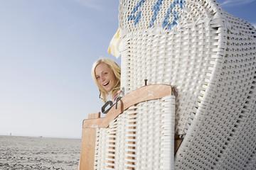 Deutschland, Schleswig Holstein, Amrum, Frau sitzen im Strandkorb, lachen, Porträt