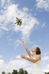 Deutschland, Bayern, Junge Braut werfen einen Blumenstrauß in den Himmel