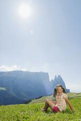Italien, Südtirol, Seiseralm, Mädchen sitzen in der Wiese