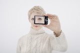 woman photographing self with digital camera