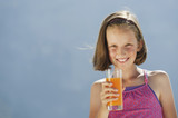 italy, south tyrol, girl (10-11) holding glass with juice, smiling, portrait