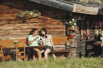 Italien, Südtirol, Paare vor Blockhaus Wein trinken, Portrait