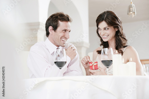 couple sitting at table in restaurant, woman holding gift parcel